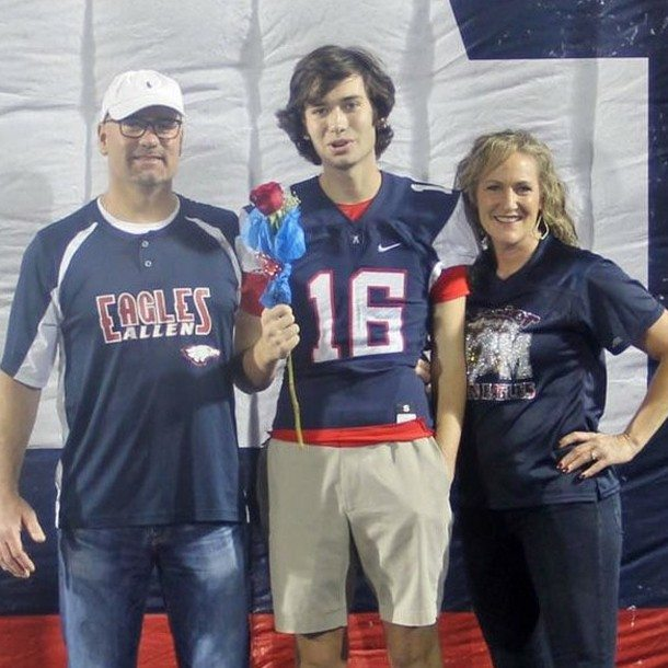 Zach and his parents at a football game